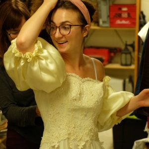 Director Olivia helps cast member Emily with her costume